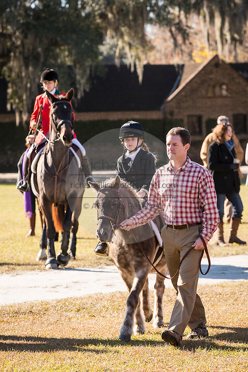 A young girl is escorted at the start of her first fox hunt at the annual Blessing of the Hounds at Middleton Place Plantation November 25, 2012 in Charleston, South Carolina. Fox Hunting in South Carolina is a drag hunt which doesn't kill live foxes.