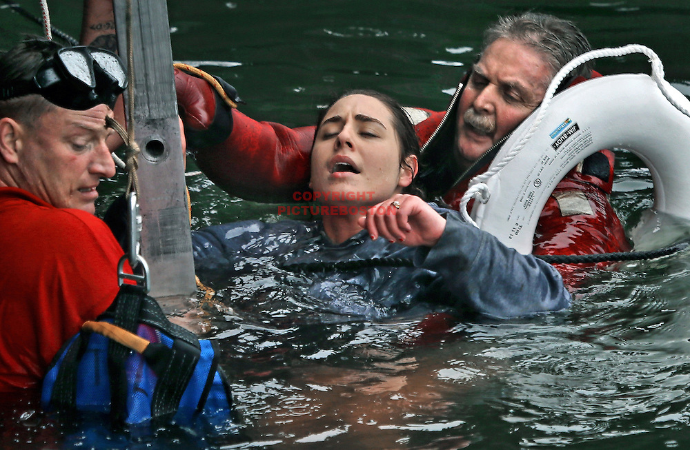 Boston firefighters, from left, John Goggin and Joseph Hughes work to rescue a woman who fell into the frigid waters of Boston Harbor on December 21, 2012. Photo: Mark Garfinkel/Boston Herald
