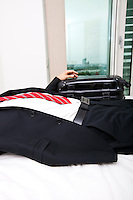 Midsection of businessman with luggage lying in bed at home