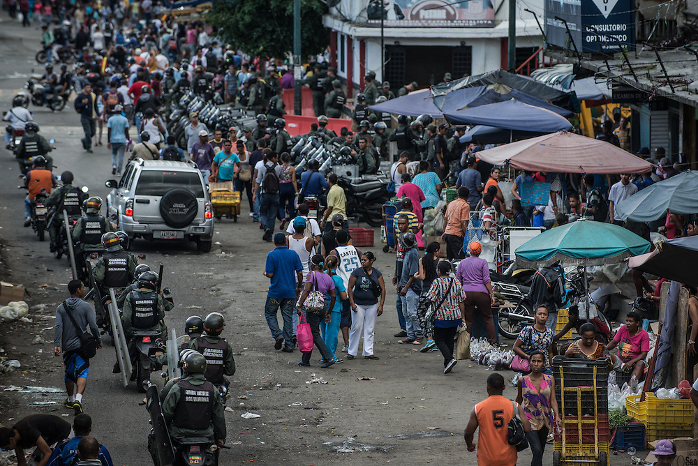 CARACAS, VENEZUELA - JUNE 9, 2016: Hundreds of National police officers and National Guard soldiers were deployed to a market in the Petare slum after a bakery and butcher shop were looted. Venezuela is convulsing from a raft of violence triggered by hunger. It is latest chapter of an economic collapse which has left the country neither able to produce its food nor import it from abroad, leaving a nation searching for how to feed itself. In the past 11 days, scores of businesses, mostly stores, have been looted or destroyed and five people have died in the confrontations. With delivery trucks under constant attack, the nation's food is now transported under armed guard. Entire cities have been militarized under an emergency decree from President Nicolás Maduro; bakeries are now watched over by the National Guard. PHOTO: Meridith Kohut for The New York Times