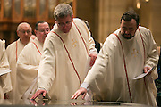 Priests leave the cathedral at the conclusion of the Chrism Mass on Tuesday, March 31, 2015.