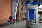 As the UK government urged that all Britons should avoid non-essential travel abroad in order to combat the Coronavirus pandemic in Britain, a rail passenger washes his hands with sanitiser by a departures information panel at St. Pancras rail station, the London terminus for Eurostar services to mainland Europe, on 17th March 2020, in London, England.