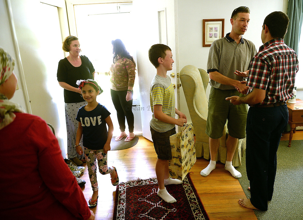 6/30/16 :: REGION :: LYNCH :: Hasan Mahmud, right, greets the Denton family, Rich, Bonnie and their son Henry, 11, into their home for Englissh lessons Thursday, June 30, 2016 in their rented Ledyard home. Hasan Mahmoud and Fahima Jemmo and their children Fidan, 17, Hanif, 15 and Fulla, 7, are refugees from the conflict in Syria and lived for three years in Turkey before finally receiving approval to come to the United States. (Sean D. Elliot/The Day)