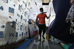 October 5, 2016 - Athens, Greece - A man cleans the floor in a sports facility at the former Athens airport of Athens, Greece on October 5, 2016Almost 2,500 migrants and refugees, mainly Afghani, are housed at the former Athens airport site, and to an olympic complex used in the 2004 Olympics. In total 60.736 refugees and other migrants are stranded in Greece. (Credit Image: © Panayiotis Tzamaros/NurPhoto via ZUMA Press)