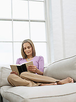 Mid adult woman reading book on sofa
