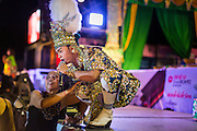 22 NOVEMBER 2013 - BANGKOK, THAILAND: A performer with the Prathom Bunteung Silp mor lam troupe poses for a photo with a fan during a performance in Bangkok. Although the show is scripted, performers leave their place in the show to go down and greet fans throughout the show. Mor Lam is a traditional Lao form of song in Laos and Isan (northeast Thailand). It is sometimes compared to American country music, song usually revolve around unrequited love, mor lam and the complexities of rural life. Mor Lam shows are an important part of festivals and fairs in rural Thailand. Mor lam has become very popular in Isan migrant communities in Bangkok. Once performed by bands and singers, live performances are now spectacles, involving several singers, a dance troupe and comedians. The dancers (or hang khreuang) in particular often wear fancy costumes, and singers go through several costume changes in the course of a performance. Prathom Bunteung Silp is one of the best known Mor Lam troupes in Thailand with more than 250 performers and a total crew of almost 300 people. The troupe has been performing for more 55 years. It forms every August and performs through June then breaks for the rainy season.     PHOTO BY JACK KURTZ