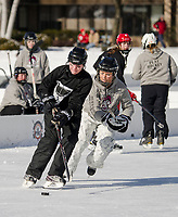 Kristin Gauthier from the Coasterz team and Nicole Currier from Jeff's Chicks battle for the puck during play action on Friday at the New England Pond Hockey Classic on Meredith Bay.  (Karen Bobotas/for the Laconia Daily Sun)
