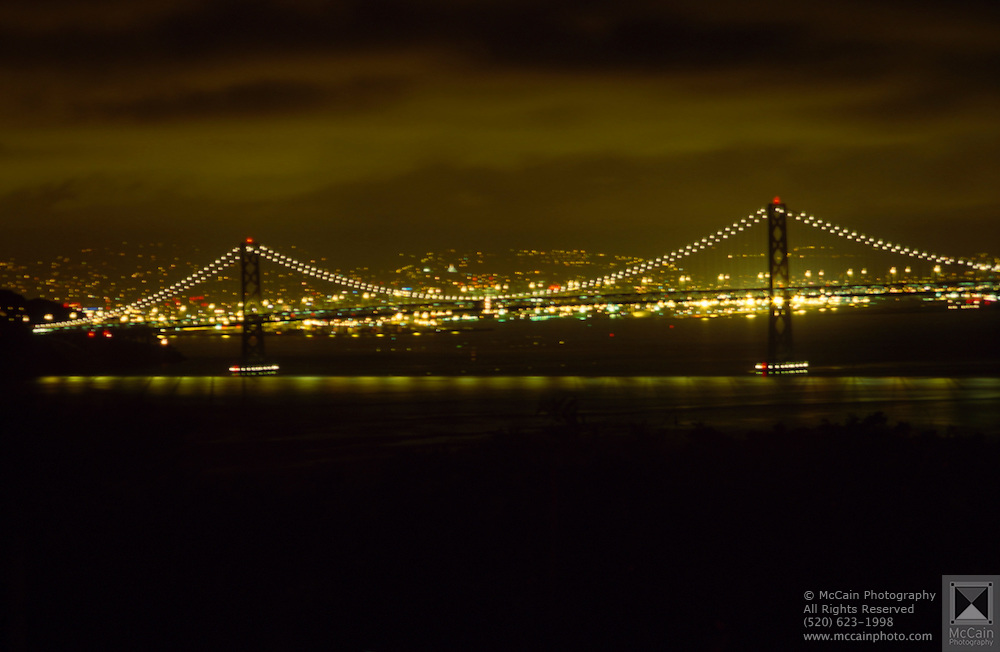 Nighttime view of the Golden Gate Bridge lit up at night with the city glowing in the background, San Francisco, California. The Golden Gate Bridge is a suspension bridge spanning the Golden Gate, the opening of the San Francisco Bay onto the Pacific Ocean. As part of both US Highway 101 and State Route 1, it connects the city of San Francisco on the northern tip of the San Francisco Peninsula to Marin County. The Golden Gate Bridge had the longest suspension bridge span in the world when it was completed in 1937 and has become an internationally recognized symbol of San Francisco and the United States..Subject photograph(s) are copyright Edward McCain. All rights are reserved except those specifically granted by Edward McCain in writing prior to publication...McCain Photography.211 S 4th Avenue.Tucson, AZ 85701-2103.(520) 623-1998.mobile: (520) 990-0999.fax: (520) 623-1190.http://www.mccainphoto.com.edward@mccainphoto.com.