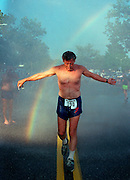 A rainbow appears as a runner in the Harry Chapin 5K race cools down under the spray of a fire department hose in Huntington, N.Y.