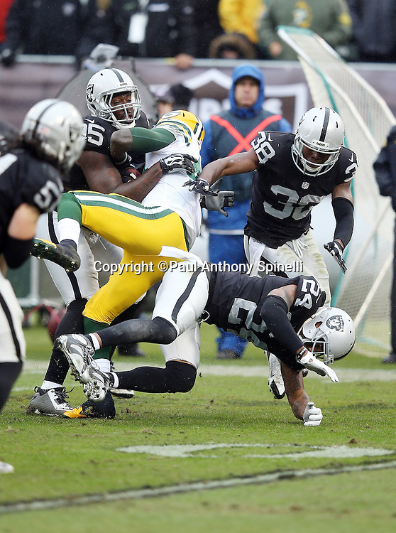Oakland Raiders free safety Charles Woodson (24), Oakland Raiders strong safety T.J. Carrie (38) and Raider teammates gang tackle Green Bay Packers running back James Starks (44) and cause a fumble recovered by the Raiders in the second quarter during the 2015 week 15 regular season NFL football game against the Green Bay Packers on Sunday, Dec. 20, 2015 in Oakland, Calif. The Packers won the game 30-20. (©Paul Anthony Spinelli)