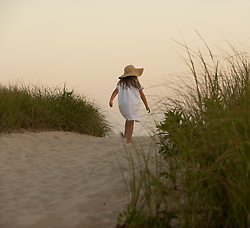little girl in a summer dress and hat walking on a sand dune in East Hampton, NY