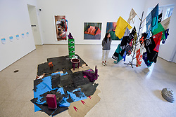 "© Licensed to London News Pictures. 13/02/2020. LONDON, UK. A staff member views a variety of student works (including on floor by Emmanuel Awuni and (R) Andrew Maughan).  Preview of ""Premiums Interim Exhibition"", an exhibition of new work by second year students in the Royal Academy Schools.   Works by 16 artists are on show 13 February to 11 March 2020 at the Royal Academy of Arts in Piccadilly by artists at the interim point of their postgraduate study at the UK's longest established art school.  Photo credit: Stephen Chung/LNP"