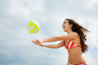 Teenage girl (16-17) playing beach volleyball low angle view