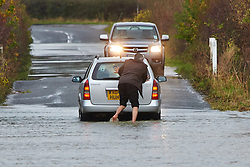 © Licensed to London News Pictures.  26/11/2012. OXFORD, UK. A man attempts to push his broken down car out of flood water on Godstow Road near Oxford. Flood warnings have been issued for the River Thames as it flows through Oxford and water levels are still rising. Photo credit :  Cliff Hide/LNP