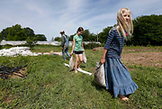 Anna Millsap, right, and Rebecca Loya carry sand bags to weigh down the tarp they just laid to kill off weeds in preparation of planting during farm camp on Wednesday, June 8, 2016.