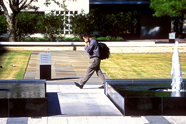 Stock photo of a man walking by a fountain and talking on his cell phone