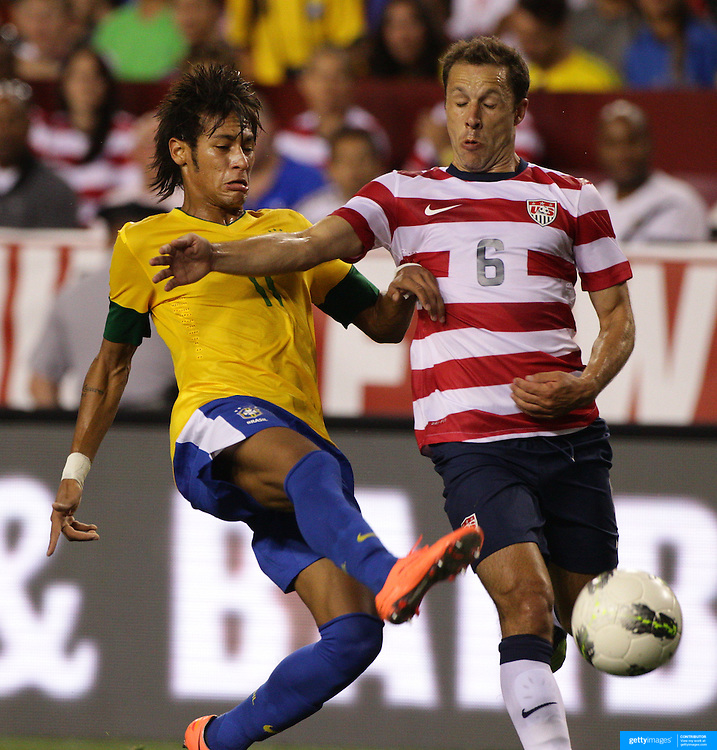 Neymar, Brazil, (left) is challenged by Steve Cherundolo, USA, during the USA V Brazil International friendly soccer match at FedEx Field, Washington DC, USA. 30th May 2012. Photo Tim Clayton