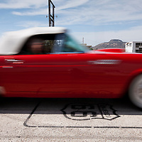 USA, New Mexico, Tucumcari, Red Vintage car drives over Route 66 marker on highway