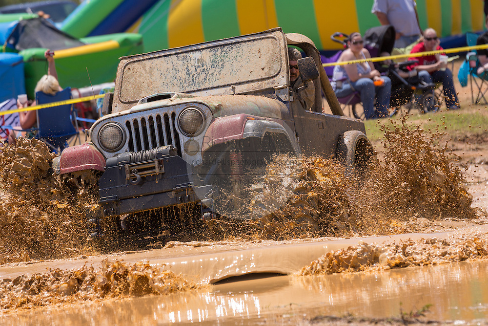 A jeep outfitted with special tires rides through a pool of mud during the Mudding Event at the 2015 National Red Neck Championships May 2, 2015 in Augusta, Georgia. Hundreds of people joined in a day of country sport and activities.