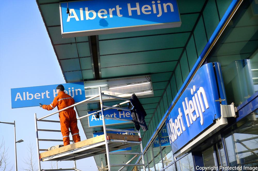 Nederland, Amsterdam, 22 januari 2013.Een bord boven de ingang van de Albert Heijn op IJburg wordt uit een lichtbak gehaald om een lamp te vervangen.