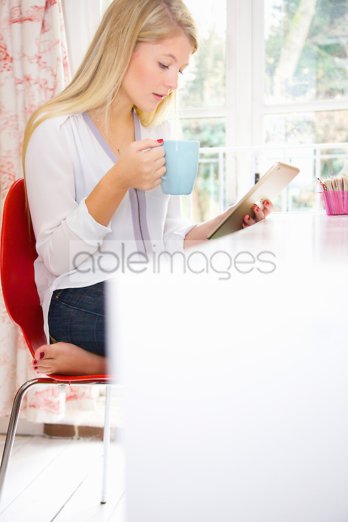 Woman Using Tablet Computer whilst Having Hot Drink