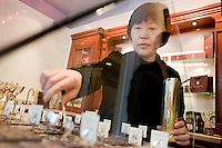 """24 October, 2008. New York, NY. Owner Namhee Girerd Kim, 53, picks an assortment of bon bons and fills a small bag at the boutique """"L'atelier du chocolat"""". The chocolates are made by her husband, Eric Girerd.<br /> NOTE: Since no customers were at the shop, the subject posed for the photographer.<br /> ©2008 Gianni Cipriano for The New York Times<br /> cell. +1 646 465 2168 (USA)<br /> cell. +1 328 567 7923 (Italy)<br /> gianni@giannicipriano.com<br /> www.giannicipriano.com"""
