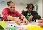 Lysette Cooper, left and Nicole Haskins, right, work on an exercise during the New and Emerging Leaders Institute, July 15, 2014.