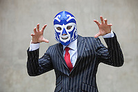 Young businessman gesturing in wrestling mask and pinstripes suit over gray background