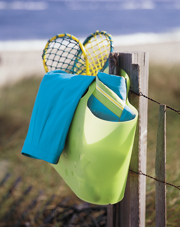 A photograph of a beach bag hanging on a fence, with the beach and ocean behind it, as if it's owners were going to play in the sand. Created for Mark, Fore & Strike.