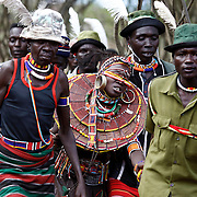 Pokot men carry a girl away to be married to a member of the group after the group came to take her.