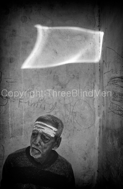 Chennai. Man with reflected light on wall.