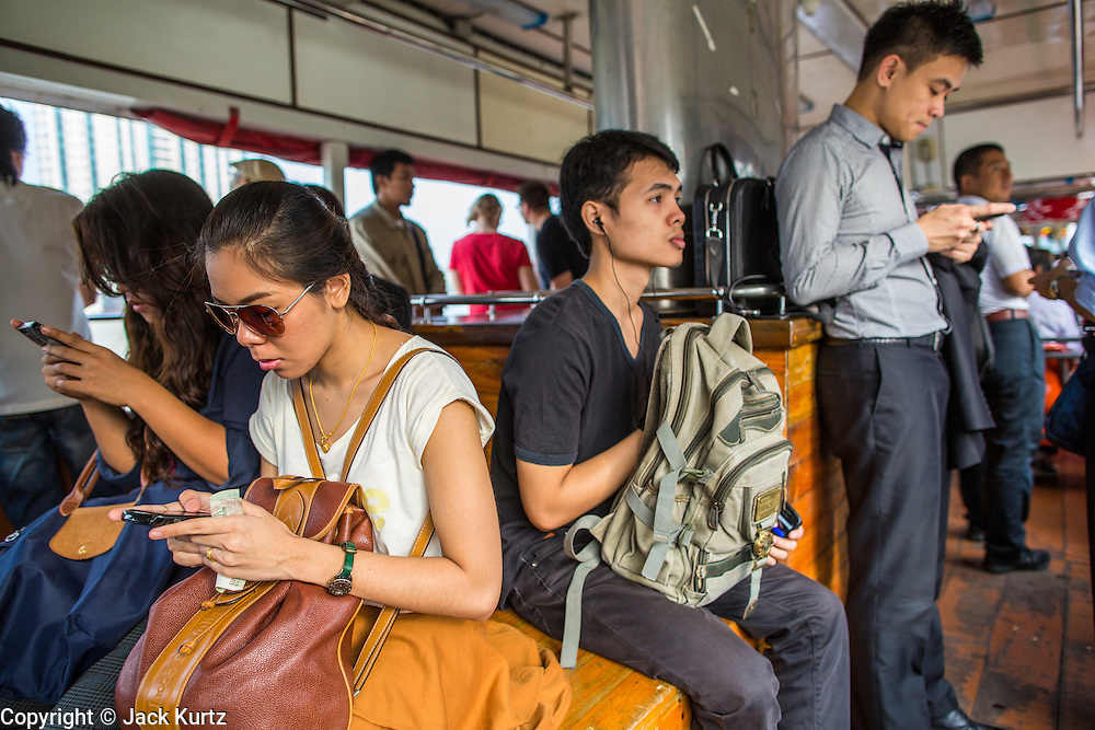 21 NOVEMBER 2012 - BANGKOK, THAILAND:  Passengers on the morning commute on a Chao Phraya Express boat in Bangkok. The Chao Phraya Express boats run up and down the Chao Phraya River in Bangkok providing a sort of bus service for neighborhoods near the river. The boats are the fastest way to get from north to south in Bangkok. Thousands of people commute to work daily on the Chao Phraya Express Boats and fast boats that ply Khlong Saen Saeb. Boats are used to haul commodities through the city to deep water ports for export.   PHOTO BY JACK KURTZ