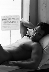 nude man resting at home by a sign muscle beach