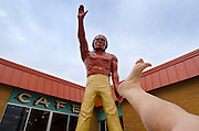 Footograph: Photograph of my right foot greeting giant fiberglass statue of a Native American Indian outside the front door of the Chieftain Motel in Carrington, North Dakota USA