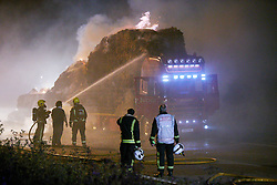 © Licensed to London News Pictures.  06/09/2012. AYLESBURY, UK. Fire fighters deal with a large hay lorry fire on the A41 near Aston Clinton. The driver Philip Judge (pictured second left) attempted unsuccessfully to shed the burning hay leaving a trail some 200 metres long before abandoning his lorry and escaping uninjured. Photo credit :  Cliff Hide/LNP
