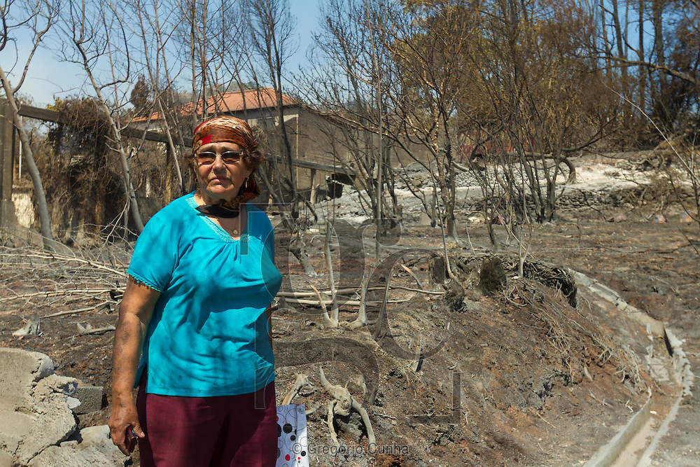 PORTUGAL, Gaula : An elderly woman stands in a burned place after a fire broke out in Gaula, some 20 km from Funchal, on Madeira Island, on July 20, 2012. Fires raged around the towns of Calheta, Ribeira Brava as well as in Santa Cruz, where one house was destroyed and a health centre, school and youth centre were evacuated as a precautionary measure. The problems started on July 18 evening when high temperatures and strong winds fanned a fire that broke out on the edge of the capital Funchal, gutting two houses and partially burning a third. PHOTO / GREGORIO CUNHA
