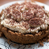 A Banoffee pie on  wooden kitchen table on a white plate.