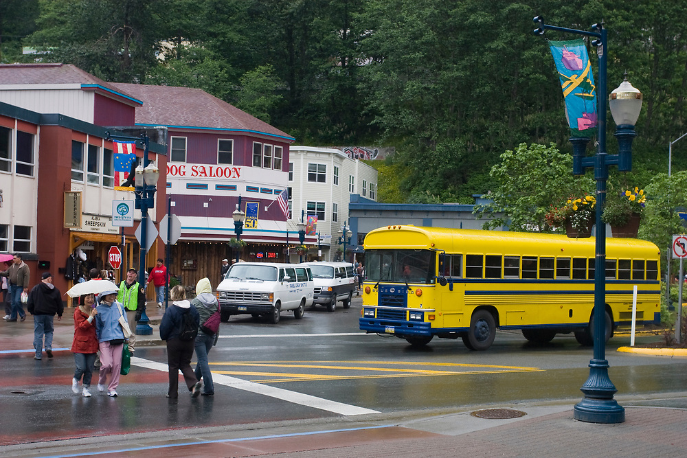 A rainy day in downtown Juneau shows tourists crossing a street and a bright yellow tour bus.