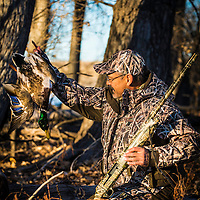 duck hunter in the brush holding up duck