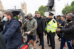 © Licensed to London News Pictures. 07/06/2020. London, UK. A group of un-identified men are escorted away by police officers after surrounding Sir Winston statue in Parliament Square against protesters for the group Black Lives Matter for the American George Floyd who died whilst being arrested by US policemen Derek Chauvin. His death has caused civil unrest in some US cities. Photo credit: Ray Tang/LNP