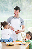 Happy father preparing food with little daughters at home