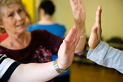 Close up of day service users hands doing a dance move whilst Day Service Officer looks on,