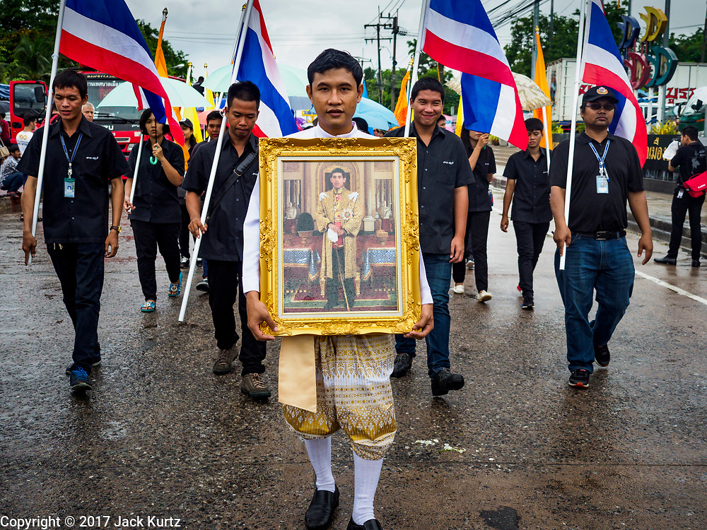 04 OCTOBER 2017 - CHONBURI, CHONBURI, THAILAND: A man carries a portrait of His Majesty King Maha Vajiralongkorn Bodindradebayavarangkun, the new King of Thailand, in the parade before the races. Contestants race water buffalo about 100 meters down a muddy straight away. The buffalo races in Chonburi first took place in 1912 for Thai King Rama VI. Now the races have evolved into a festival that marks the end of Buddhist Lent and is held on the first full moon of the 11th lunar month (either October or November). Thousands of people come to Chonburi, about 90 minutes from Bangkok, for the races and carnival midway.   PHOTO BY JACK KURTZ