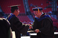 Interim Graduate School dean Peter Harries (right) congratulates a doctoral graduate.