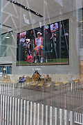 City workers watch a womens' tennis match on a huge screen outside the City of London headquarters of insurance company Aviva during Wimbledon fortnight, on 4th July, London, United Kingdom. Seen through the large window of Aviva's foyer, reflections of City buildings as well as visitors to the building merge with the tennis action.