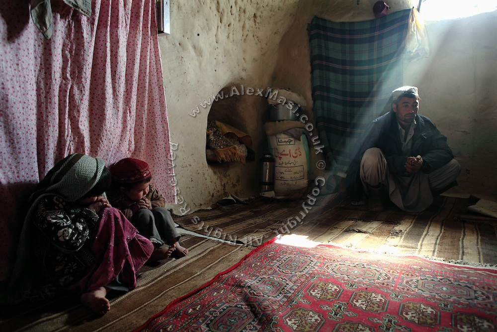 Sakhi Ullah, 30, is sitting in one of his neighbours' cave while Monirah, 7, (Left) and her brother Najibullah, 3, (Right) are sitting in what has been their family home since six years, in Bamyan, central Afghanistan, an area mostly populated by Hazaras. A historically persecuted minority (15%) due to more lenient Islamic faith and characteristic 'Eastern' lineaments, Hazaras constitute the 70% of Bamyan's population.