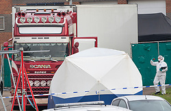 © Licensed to London News Pictures. 23/10/2019. Grays, UK. A police forensics officer looks at the front of the truck at Waterglade Industrial Park in Grays, Essex where the bodies of 39 people have been found in a lorry container. The driver, a 25-year-old-man from Northern Ireland, has been arrested on suspicion of murder. . Photo credit: Peter Macdiarmid/LNP