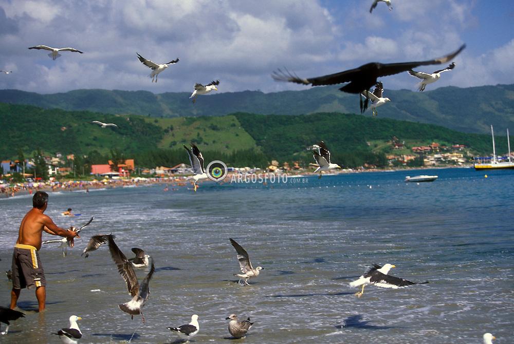Garopaba, SC, Brasil.Ano 2002.Pescador jogando restos de peixe no mar para as gaivotas./ Fisherman throwing fish in the sea to the seagulls..Foto Rubens Chaves/Argosfoto