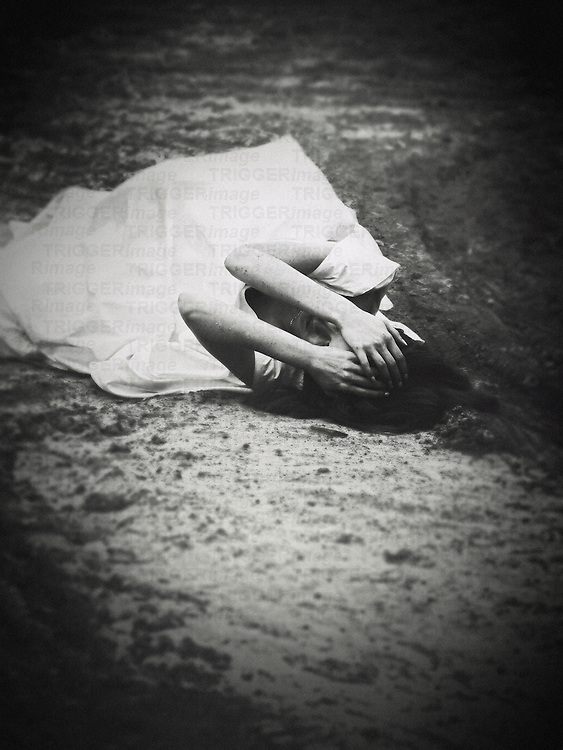 A monochromatic image of a woman in a white gown, laying on the ground in the middle of a village road, with her hands touching her head in a dramatic expression.
