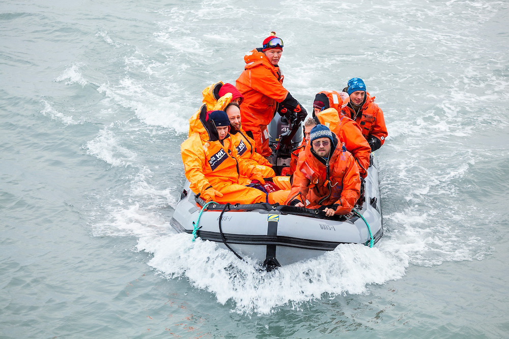 Norwegian, Russian, and Polish oceanographers participating in a science diplomacy meeting regain the MS Stalbas on an inflatable boat in Hornsund, Svalbard.
